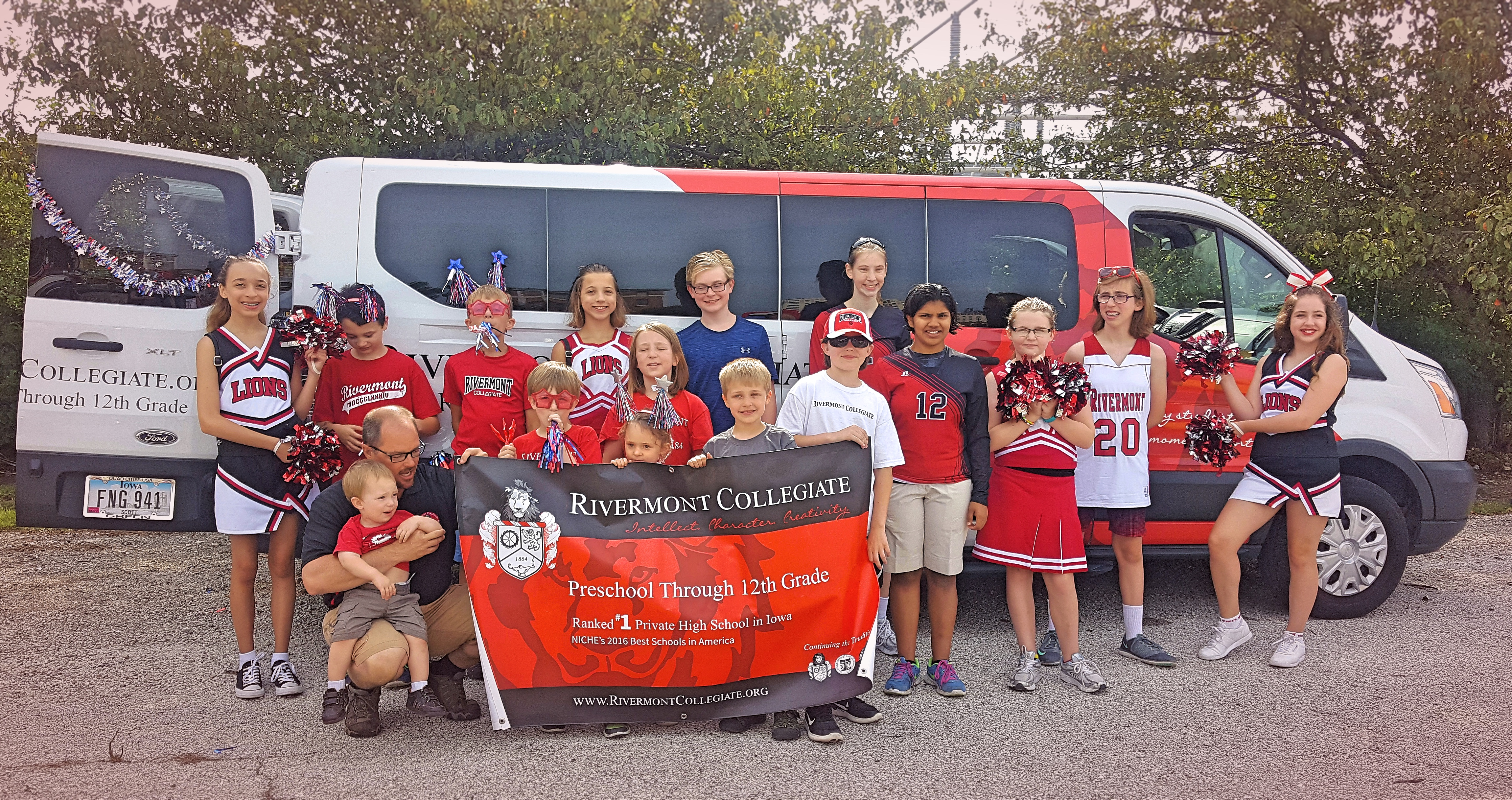 Rivermont students standing in front of the school van at the July 4th parade