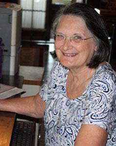 Photo of Linda Paget at  her desk