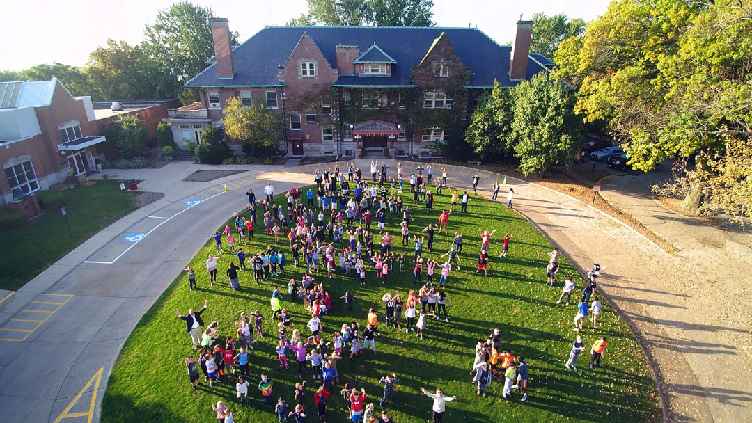 students gathered in the grassy circle waving to the drone camera